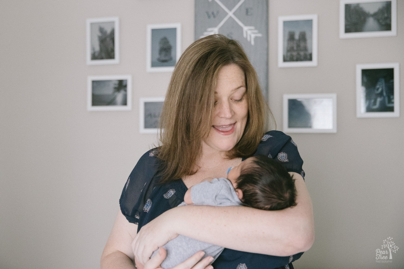 Mom holding her newborn baby boy and singing to him.