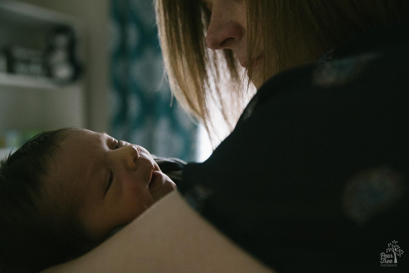 Mom holding her smiling newborn baby boy.