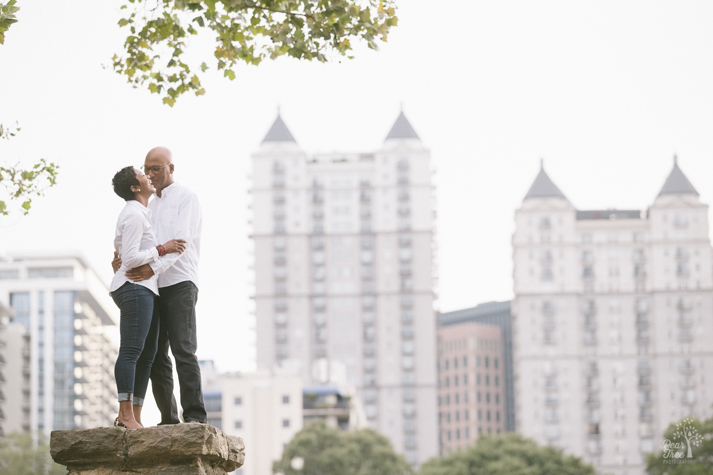 Engaged couple standing in Atlanta skyline inside Piedmont Park