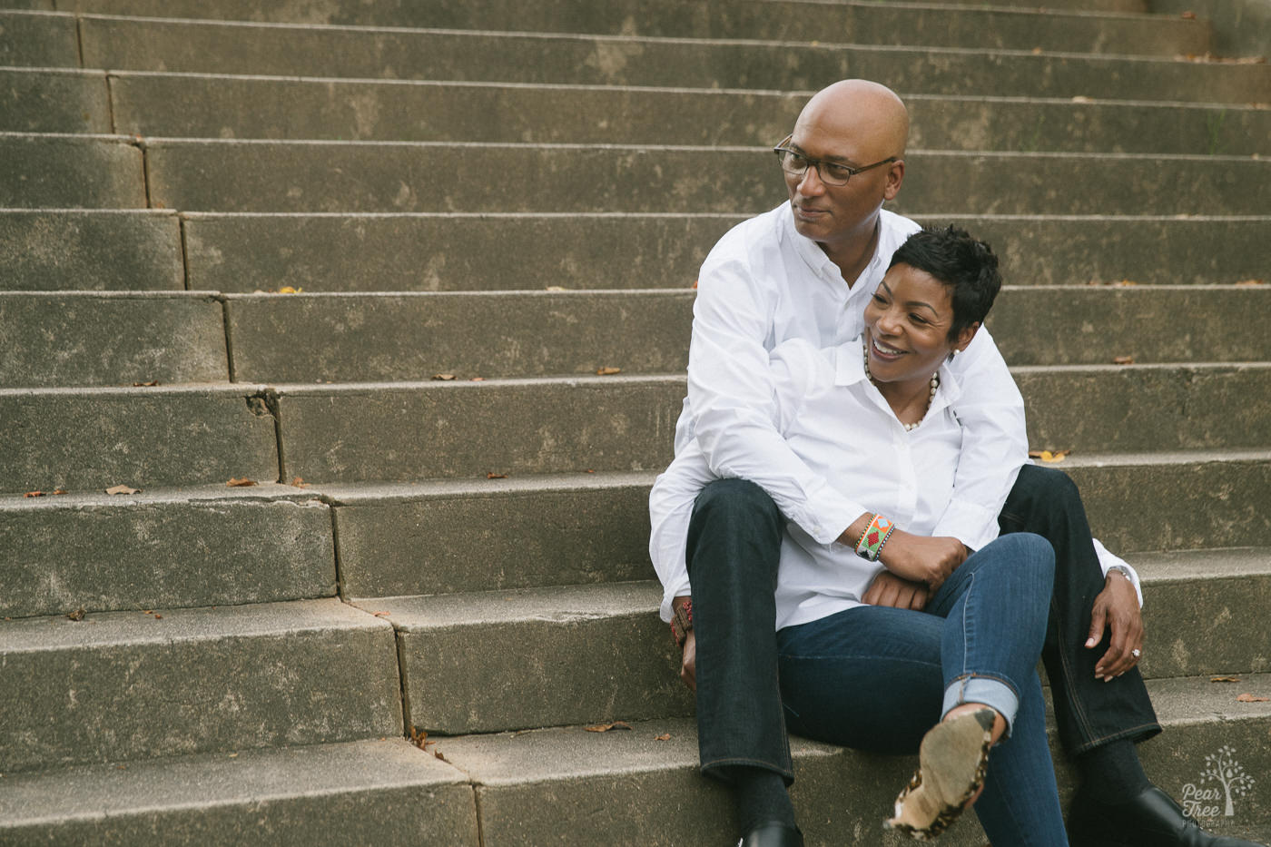 Happy engaged African American couple sitting on Piedmont Park steps holding each other.