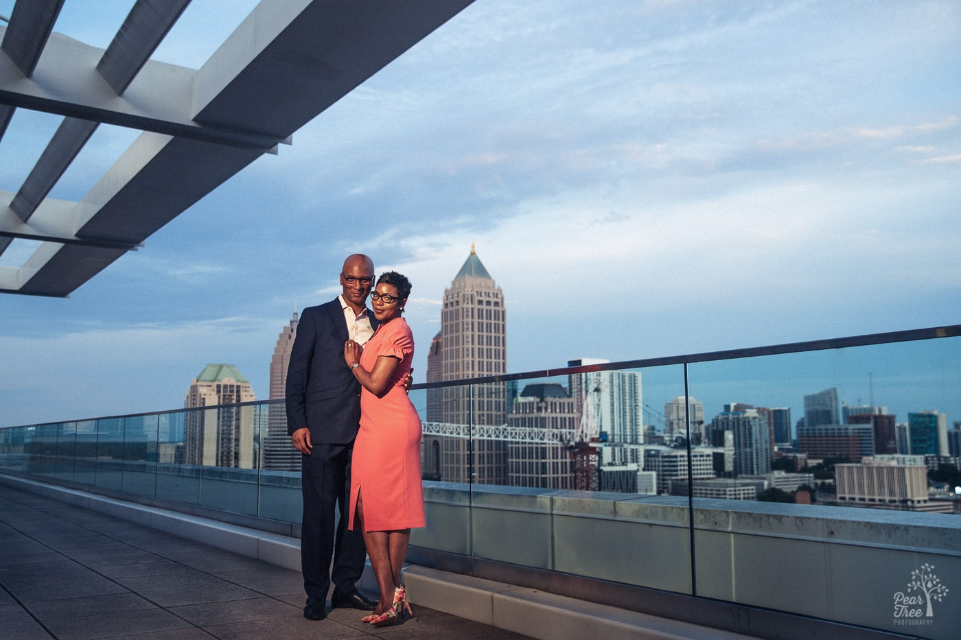 Engaged couple in fancy dress on Atlantic Station 18th floor balcony with Atlanta skyline in background
