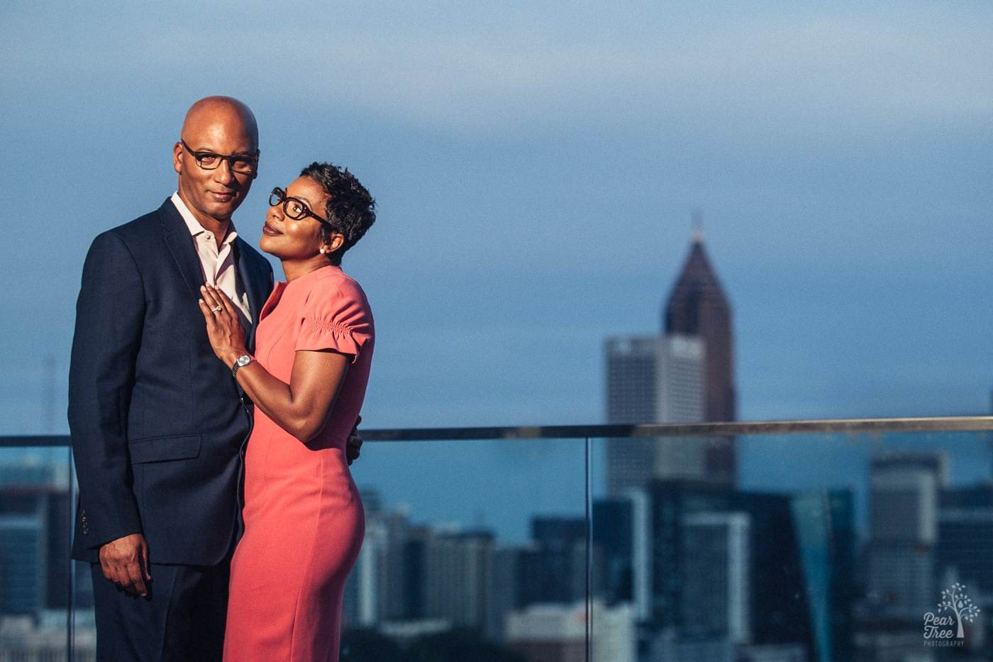 Power shot of engaged couple in Atlanta skyline from 18th floor balcony in midtown.