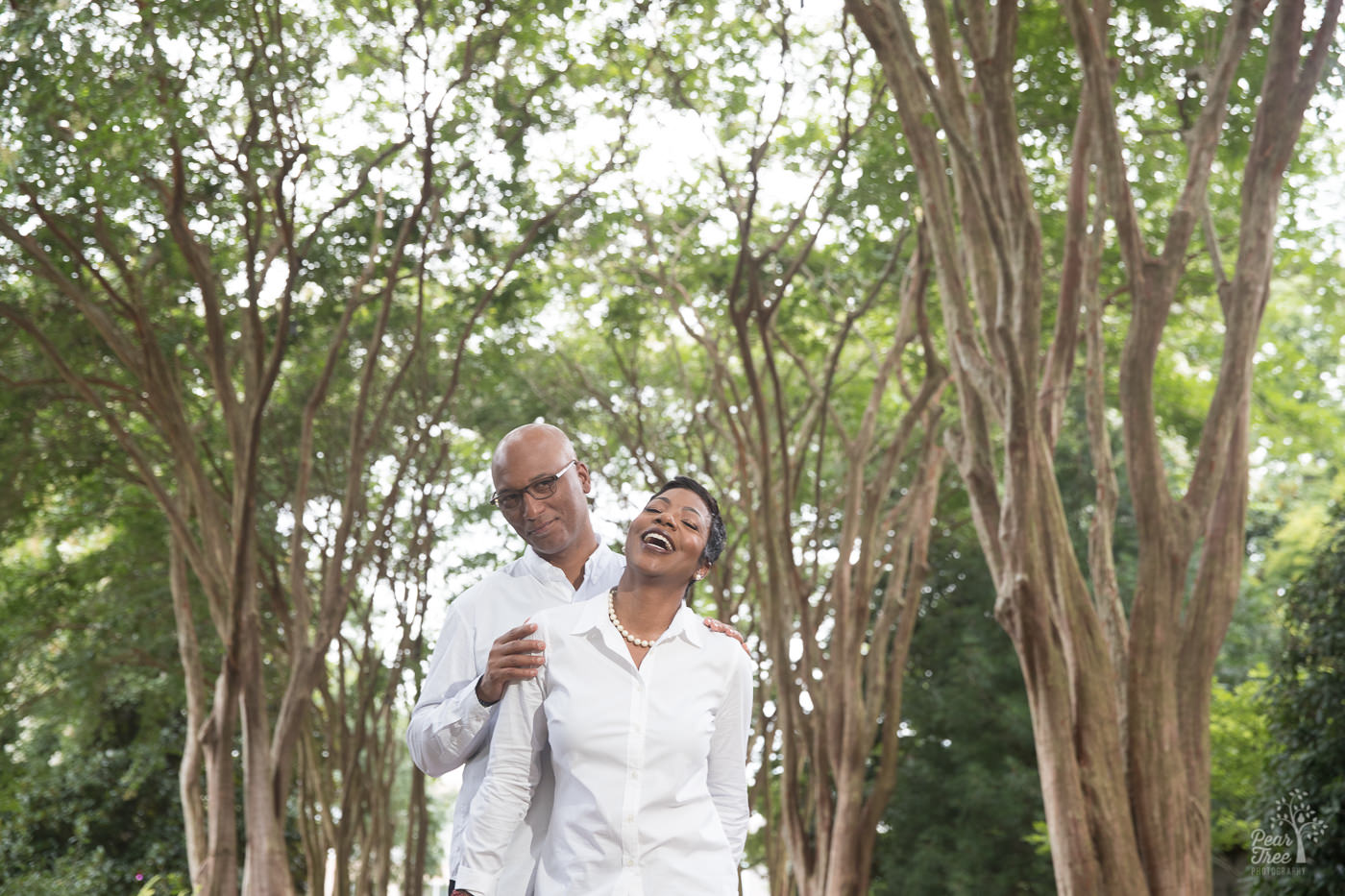 Smiling and laughing couple in middle of Atlanta Botanical Garden crepe myrtles walkway