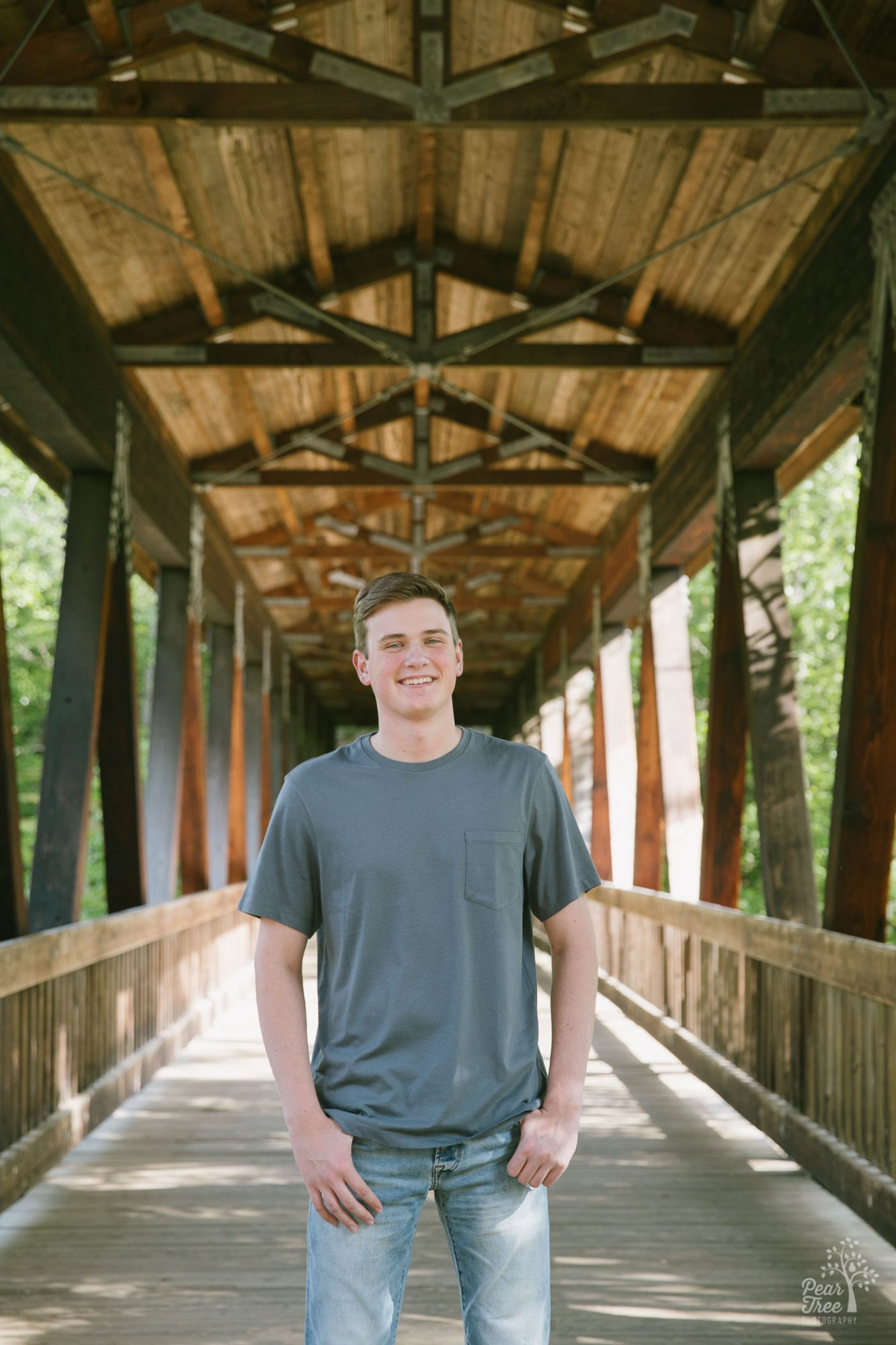 High school senior boy standing in covered bridge at Roswell Mill.