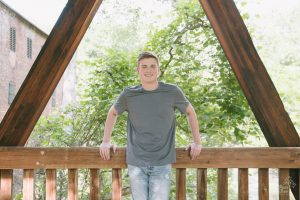 Woodstock High School senior smiling while leaning against Roswell Mill bridge railing