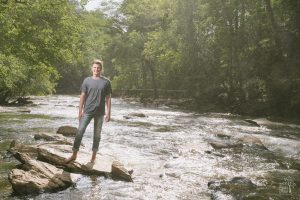 High school senior boy standing on shoals at Vickery Creek near Roswell Mill