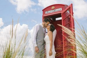 Gorgeous bride + groom kissing in front of red telephone booth with Just Married sign and blue skies