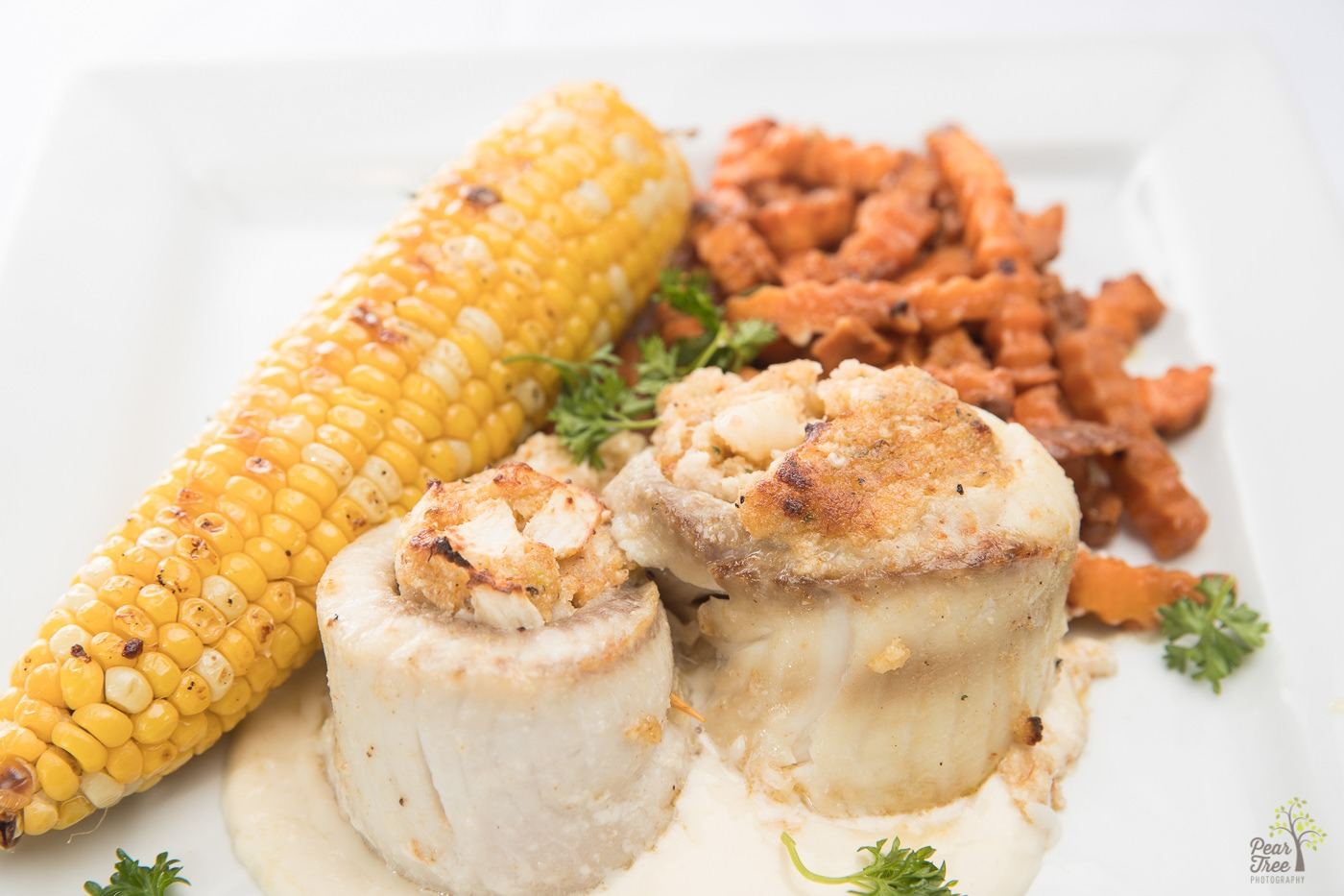 Stuffed tilapia rolls with cajun corn on the cob and crinkly sweet potato fries made by Divine Taste of Heaven.