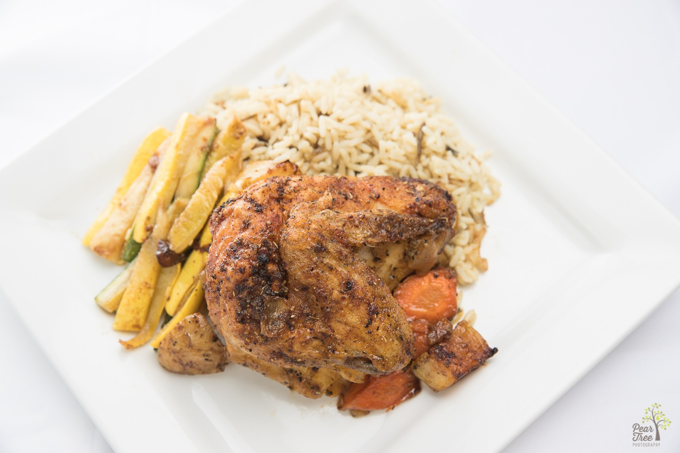 Baked chicken with zucchini, rice pilaf, and sweet carrots catered by Divine Taste of Heaven.