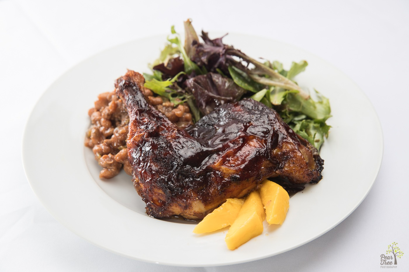 Barbecued chicken with baked beans, spring mix salad, and mango slices made by Divine Taste of Heaven.