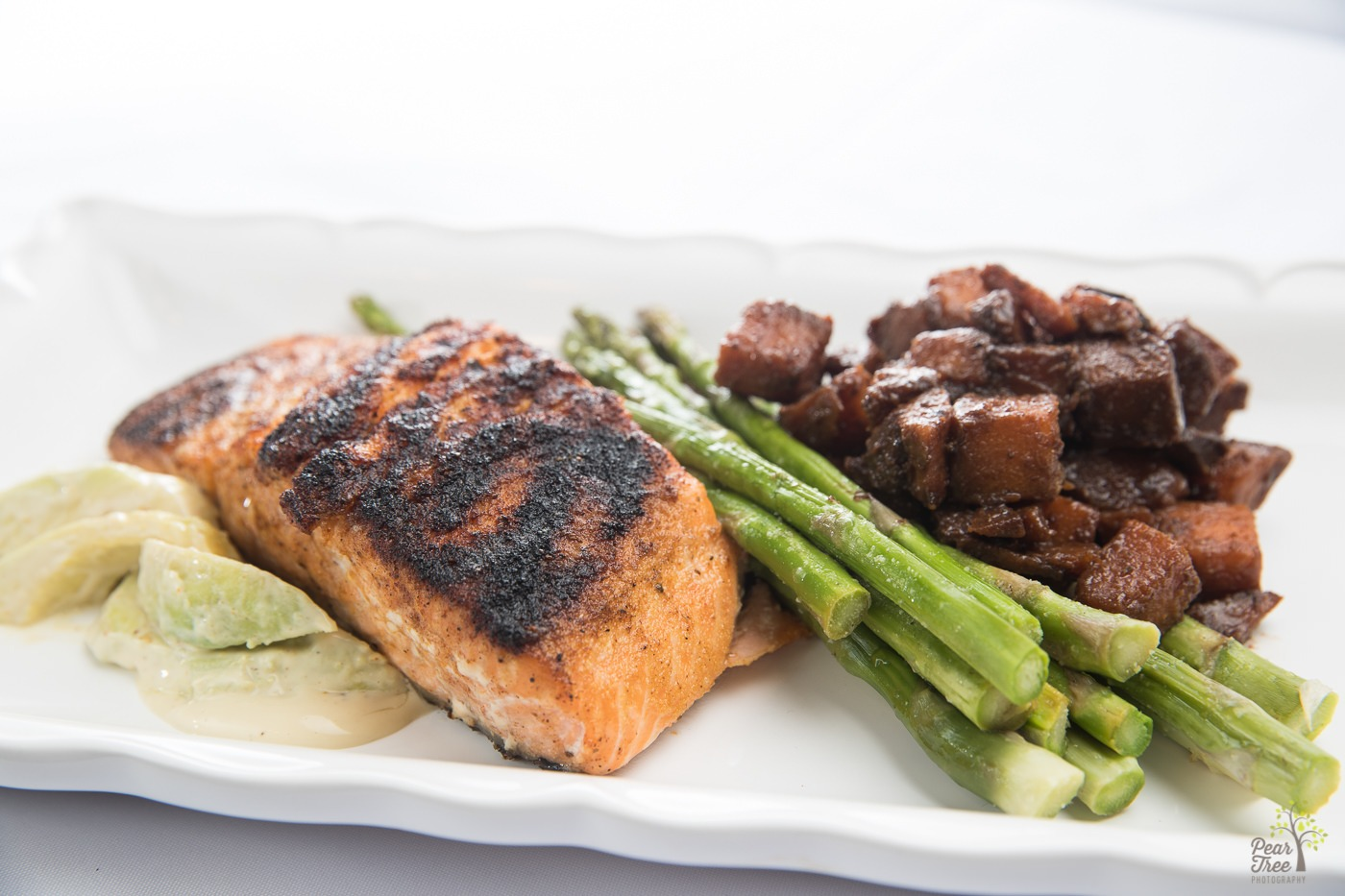 Blackened salmon with fresh asparagus, potatoes, and creamy avocado slices prepared by Divine Taste of Heaven.
