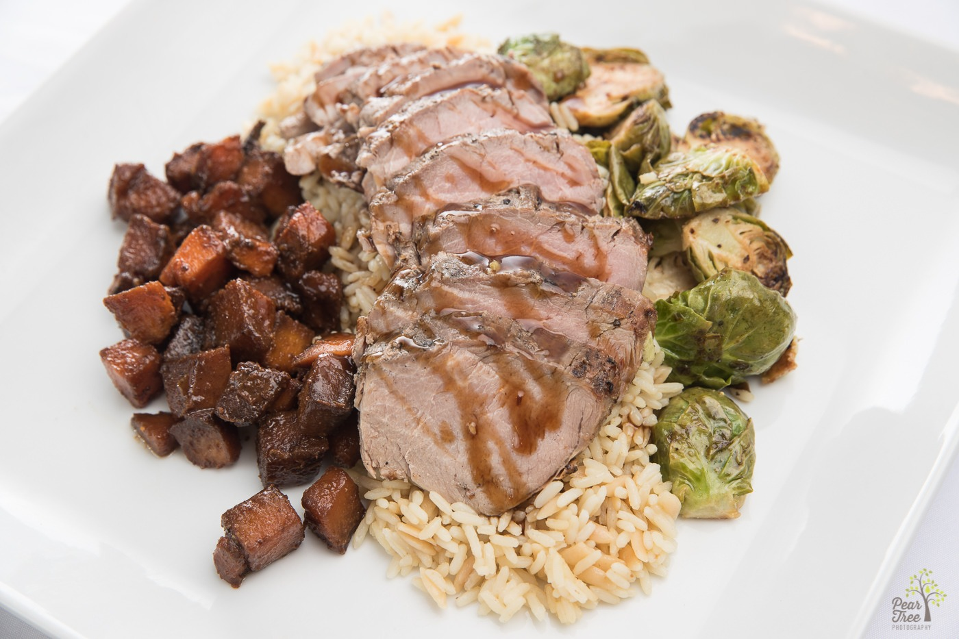 Pork tenderloin on a bed of rice served with roasted potatoes and brussell sprouts prepared by Divine Taste of Heaven.