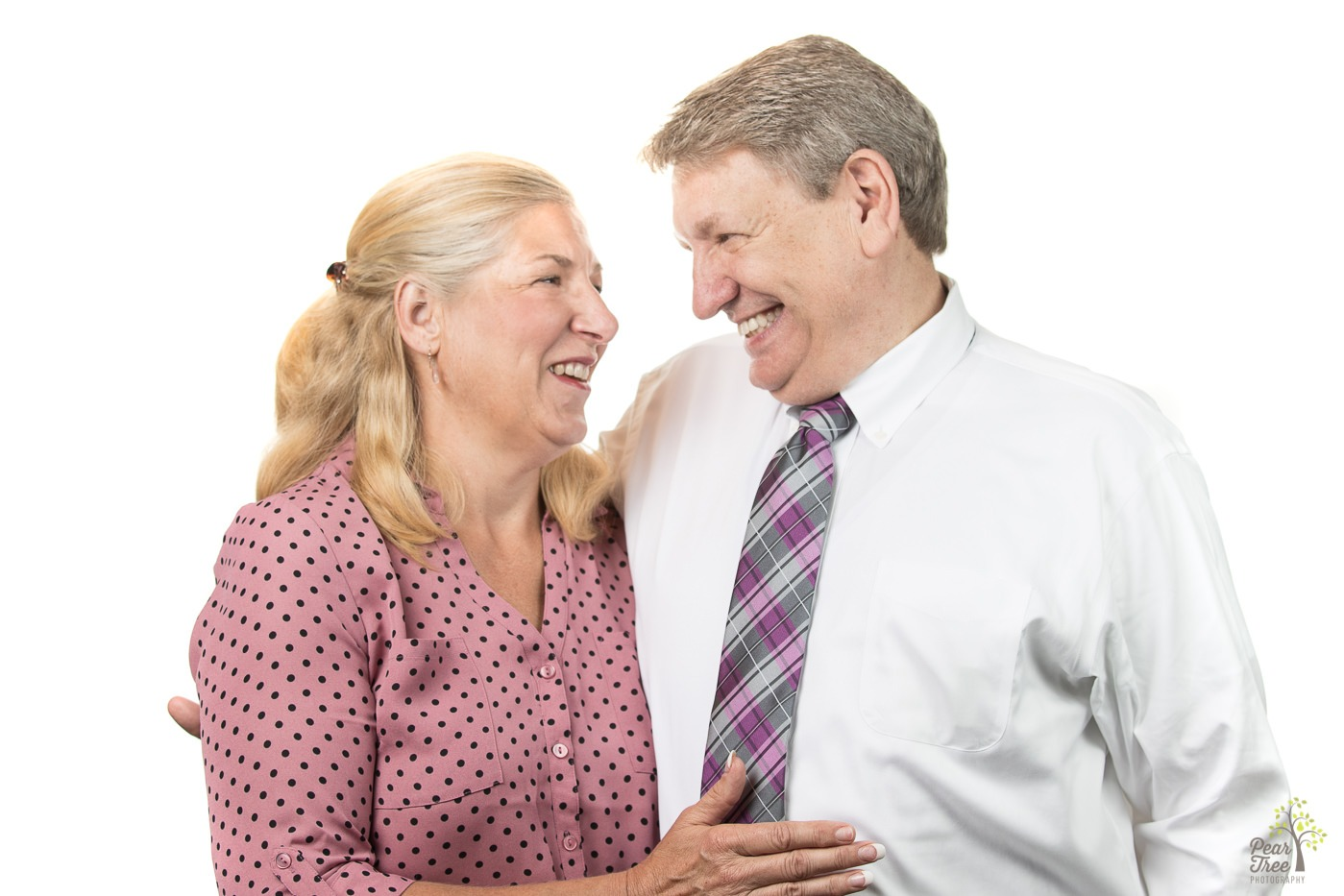 Husband and wife holding each other close and laughing at each other.