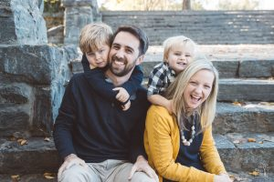 Cute family of four with two little blonde boys squeezing close and laughing on Piedmont Park steps