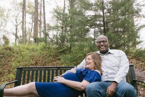 Beautiful pregnant mom in blue dress laying down on her husband's lap on a park bench