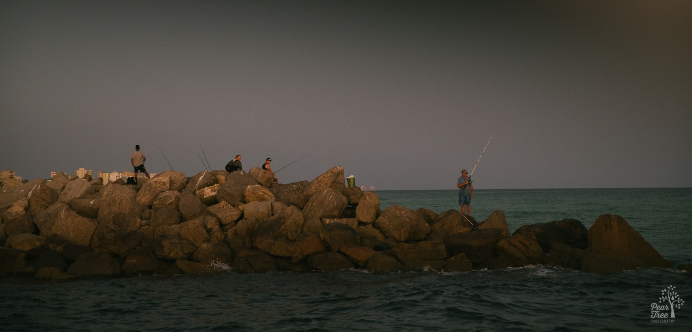 Fishermen on rocks at sunset in Destin, FL.
