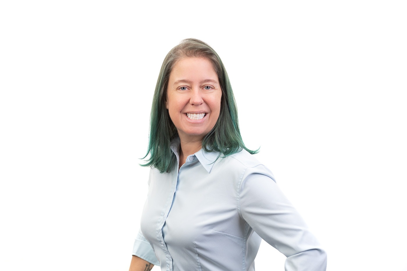 Smiling woman with teal hair and blue shirt in front of a white wall