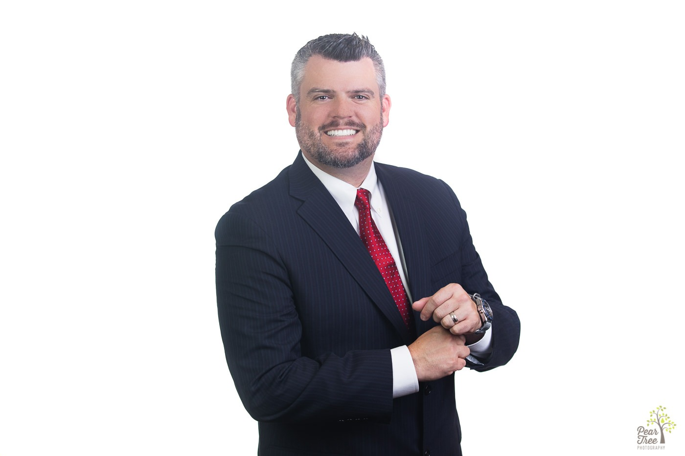 Professional headshot and branding shot of a man standing in dark suit with a red tie adjusting his sleeve