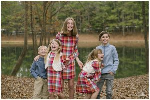 Five young cousins laughing hysterically while dressed for fall at the lake