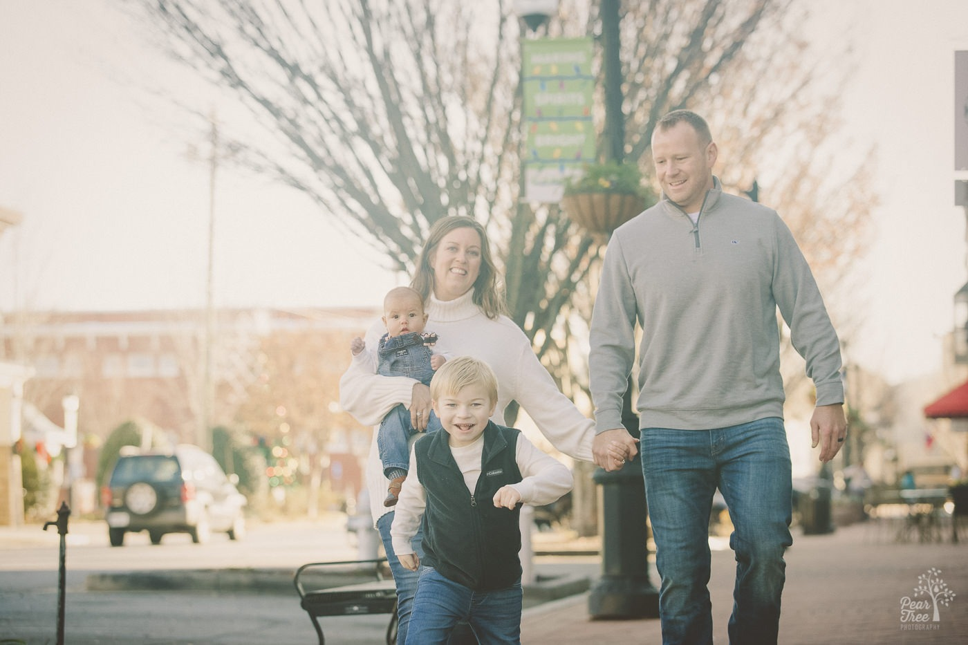 Happy family of four walking through downtown Canton at Christmastime