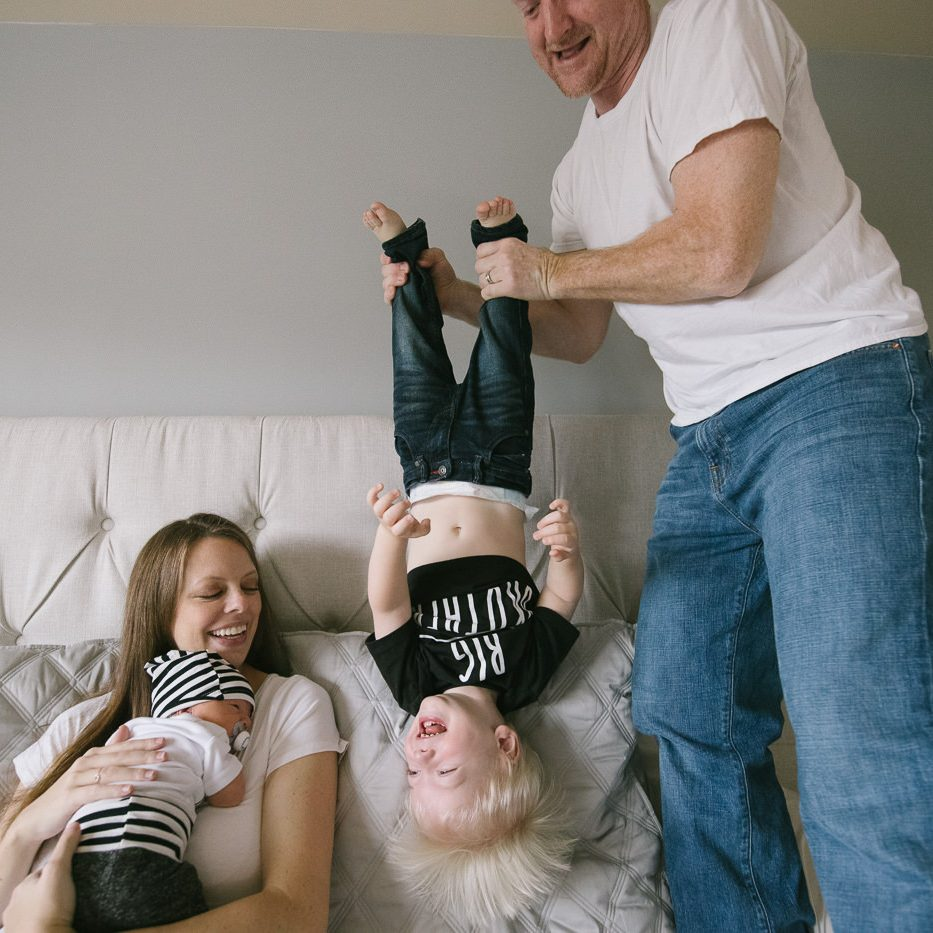 Mom holding newborn son on bed while Dad stands and holds their toddler upside down