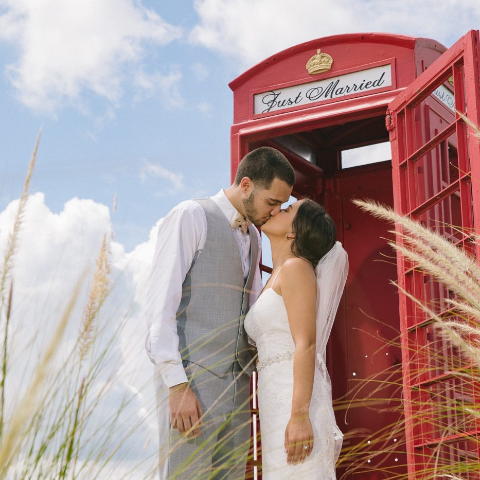 Gorgeous bride + groom kissing in front of Royal Crest Room red phone book