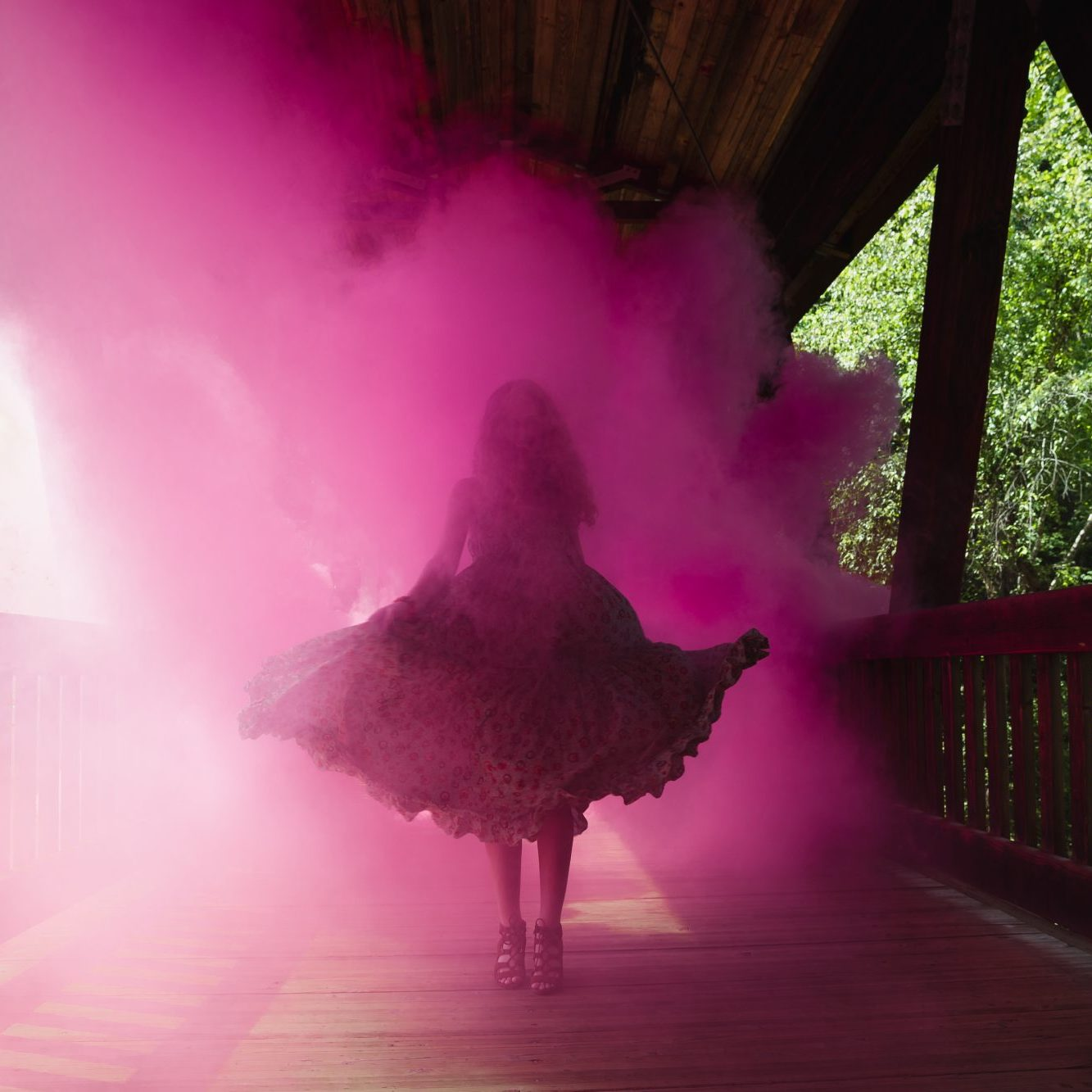 High school senior twirling in pink smoke on a covered bridge