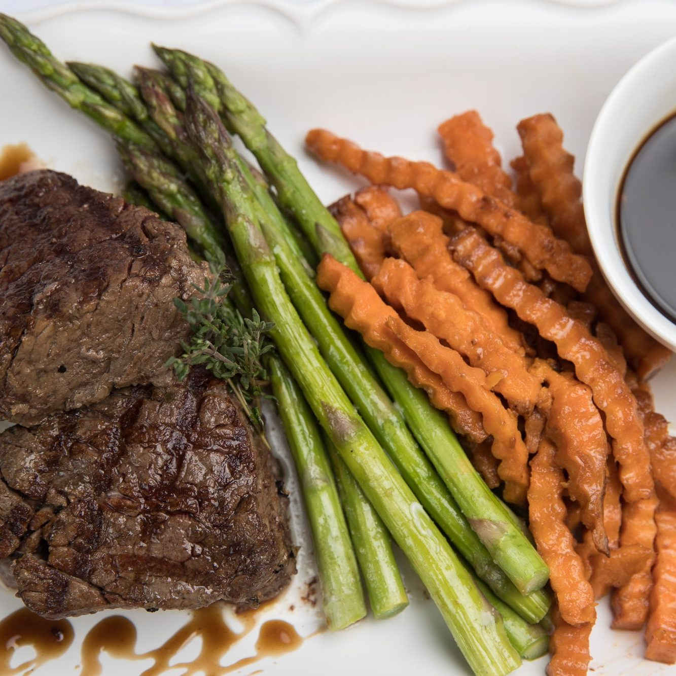 Delicious steak, asparagus, and sweet potato fries plated by Divine Taste of Heaven