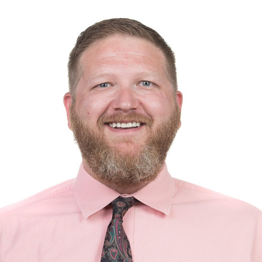 Headshot of a smiling red headed mail in pink shirt and tie