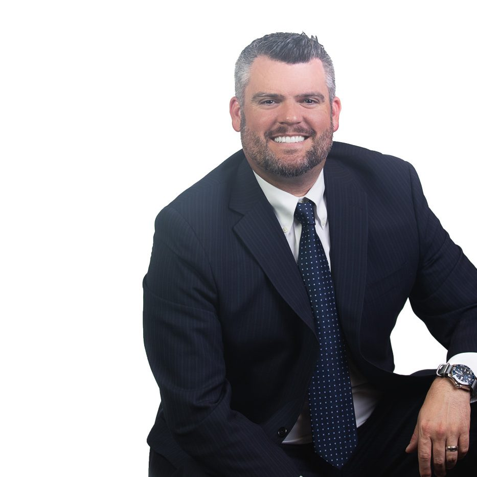 Professional headshot and branding shot of a man sitting in dark suit with a blue tie