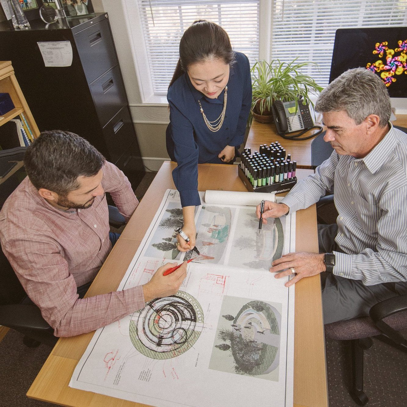 Three landscaping architects working on blueprints together at Manley Land Design office