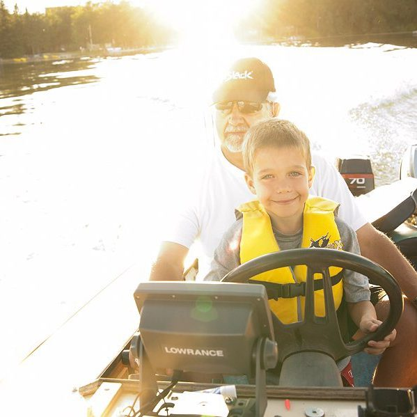 Little boy sitting in his Grandpa's lap while driving a boat across a lake at sunset.