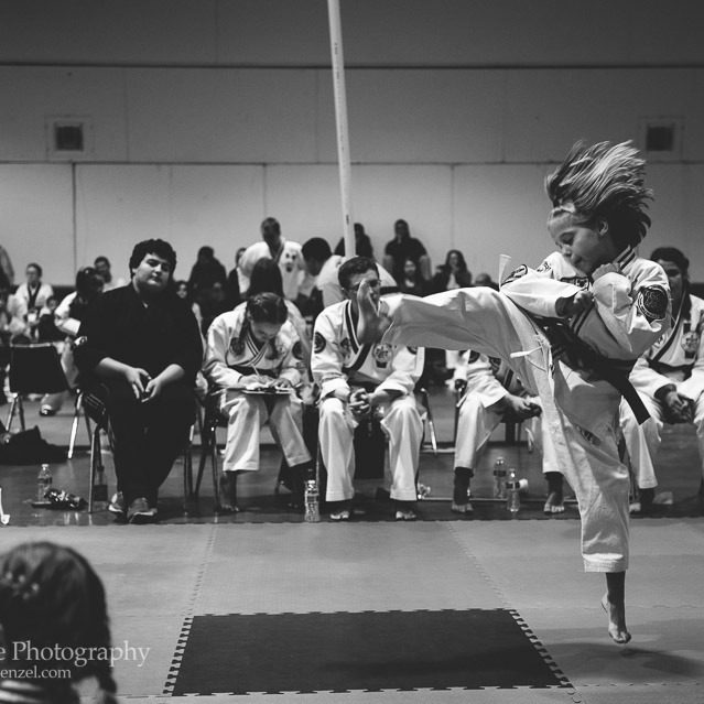 Black and white photograph of eight year old girl jumping and kicking in a karate tournament