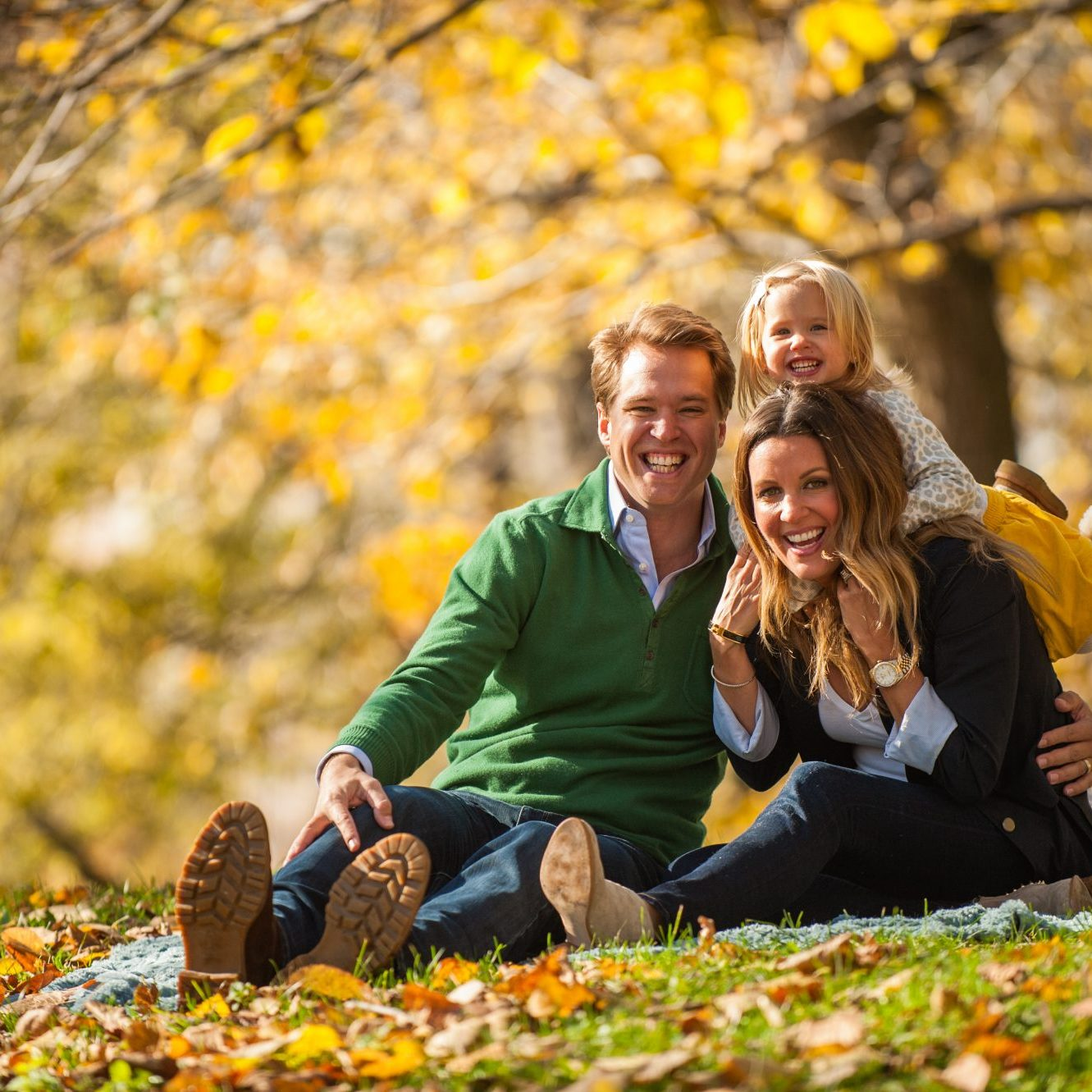 Family of three sitting and laughing together in Chicago fall leaves
