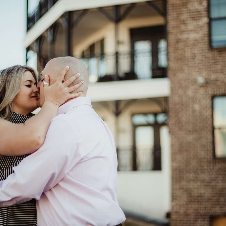 Gorgeous blond pulling her fiance close and holding his head while she goes in for a kiss at Avalon during their engagement session
