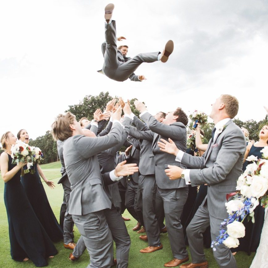 Groom being thrown into the sky above groomsmen while bride and bridesmaids watch in surprise.
