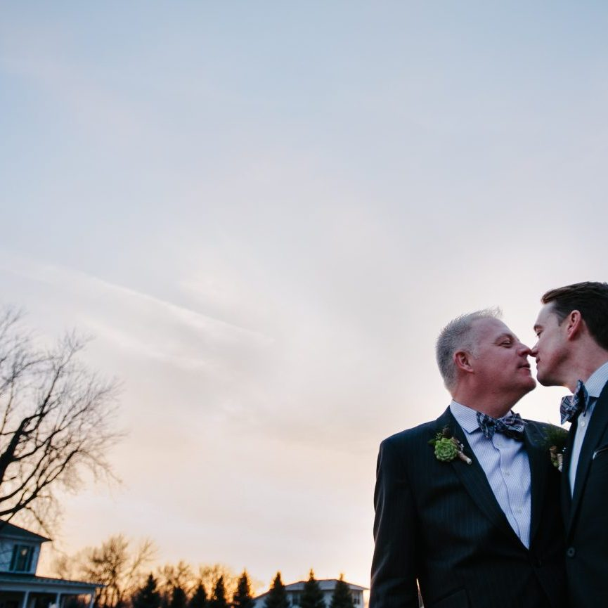 Two grooms almost kissing at sunset