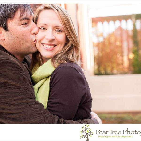 Husband holding his wife tight and smooching her on her cheek at Agness Scott College