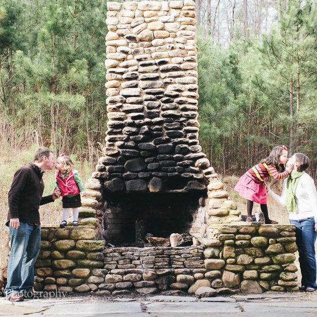 Two parents smooching their little girls on sides of Rope Mill outdoor fireplace