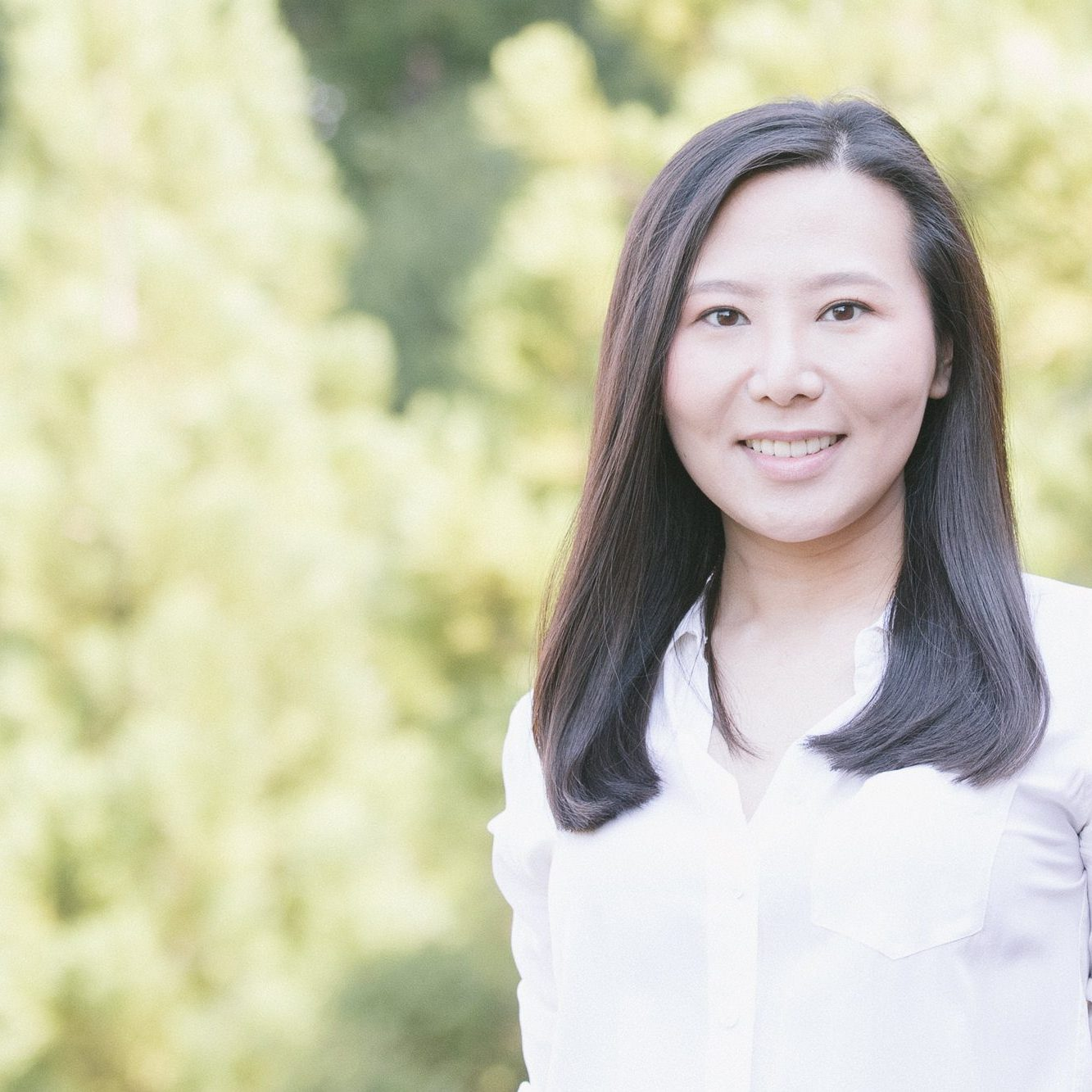 Smiling Chinese woman standing in front of out-of-focus trees