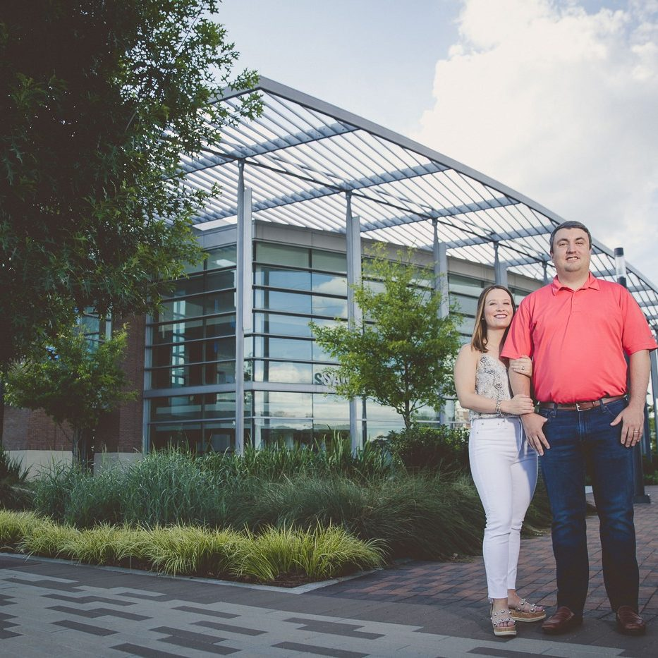 Husband and wife standing smiling in front of City Springs building with blue sky and clouds