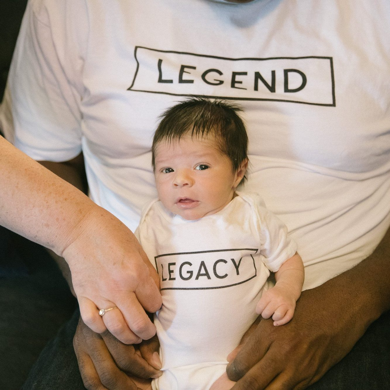 Grandma's hand is straightening out newborn's LEGACY onesie while being held by Dad in LEGEND t-shirt
